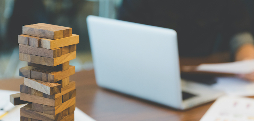 Stack of wooden blocks on a desk with open laptop