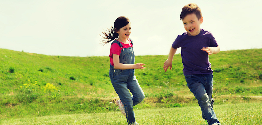 Two children playing tag outside