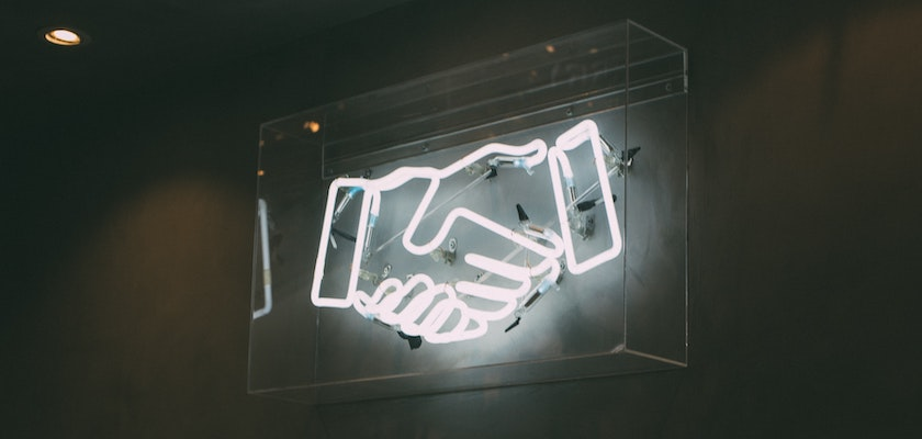 Neon light graphic of handshake representing marketing and sales partnering to drive revenue