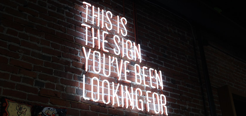 Neon sign on brick wall which says: This is the sign you've been looking for