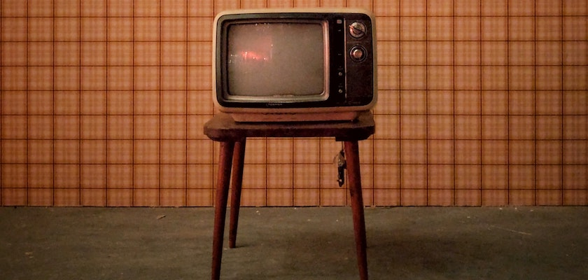 Vintage television in room with brown wallpaper