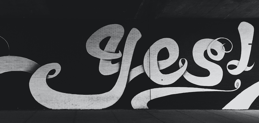 "The word ""yes"" painted in white paint on a black wall background"