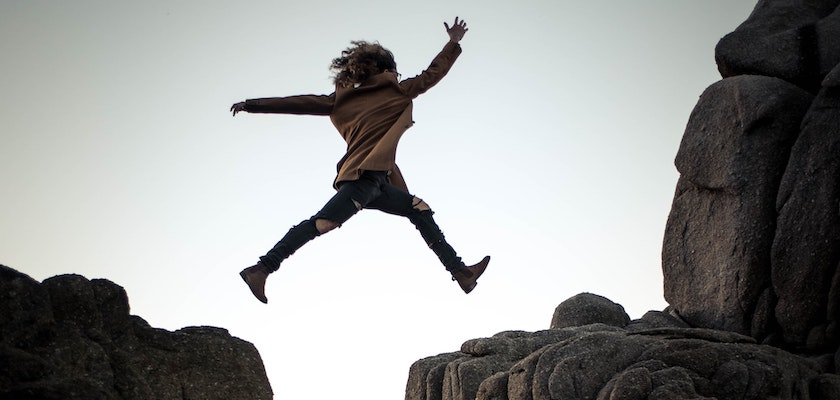 Woman jumping between two large rocks