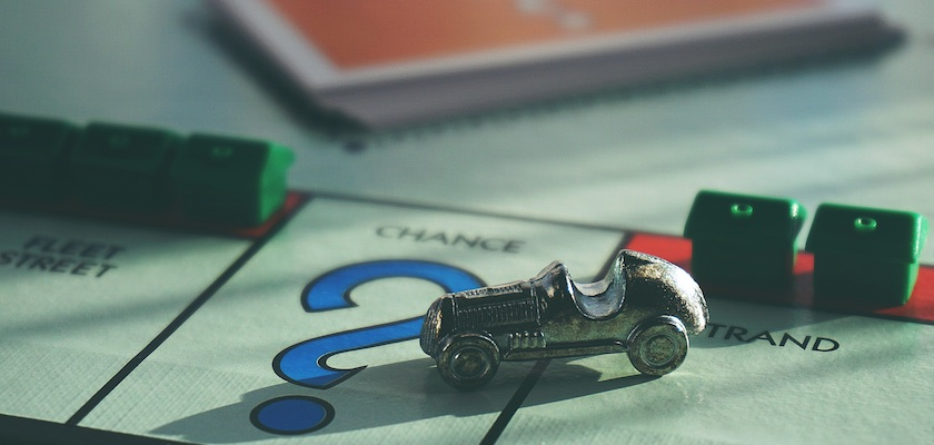 Monopoly board with car piece that has landed on the change question card