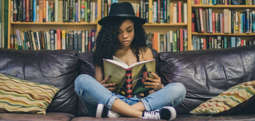 Woman wearing a hat while reading a book on a couch in front of a large book case