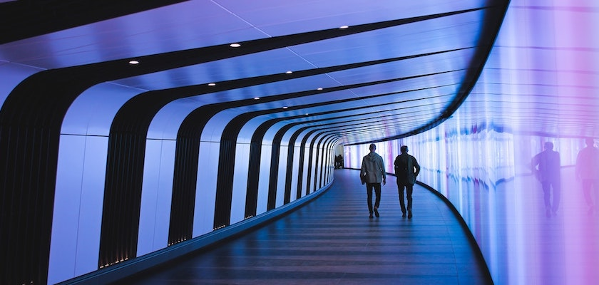 Two men walking down a purple futuristic hallway towards marketing-led customer experience