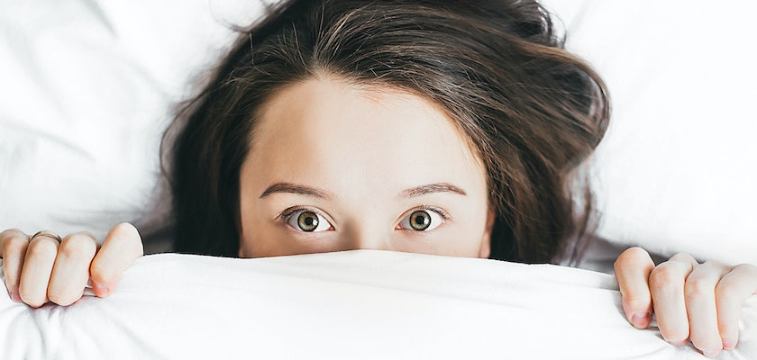 Woman hiding her face beneath a white blanket