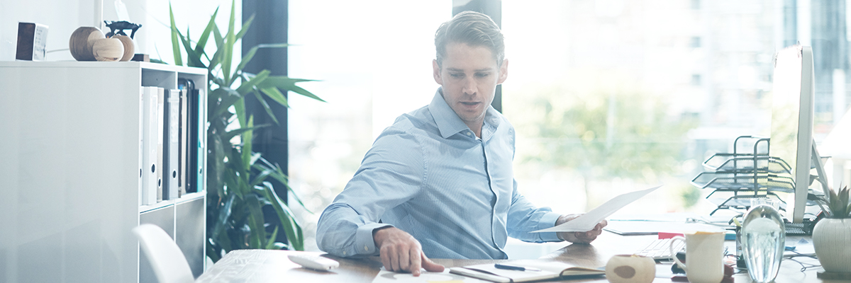 man looking at papers on his desk