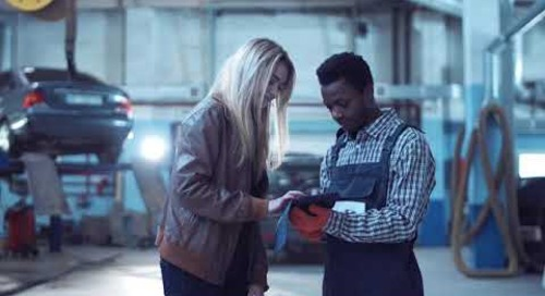 female blond client giving keys from her car to mechanic in uniform and signing on digital tablet BK